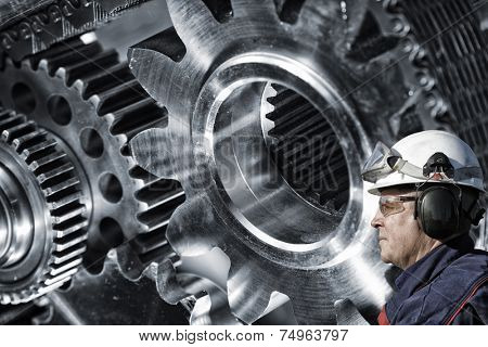 mechanic, engineer with large cogwheels machinery in background