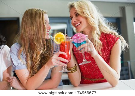 Pretty friends drinking cocktails together at the bar