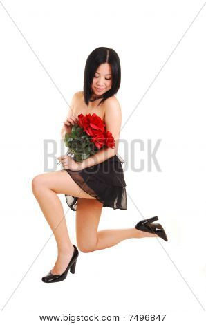 Chinese girl kneeling in black dress.