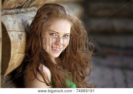 Portrait of the beautiful red haired girl and wood wall