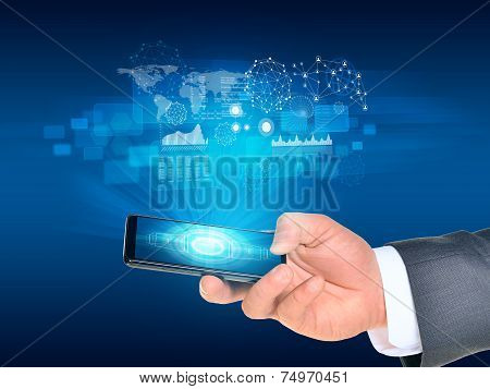 Man hand using smartphone. World map and graphs near phone