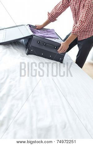 Midsection of young businessman packing suitcase in bedroom