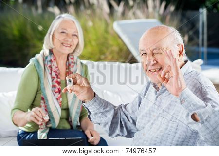 Portrait of happy senior man gesturing okay while playing rummy with woman at nursing home