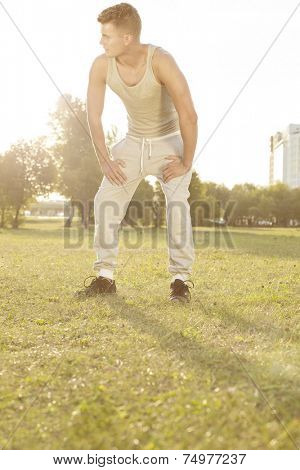 Full length of tired man standing in park after jogging