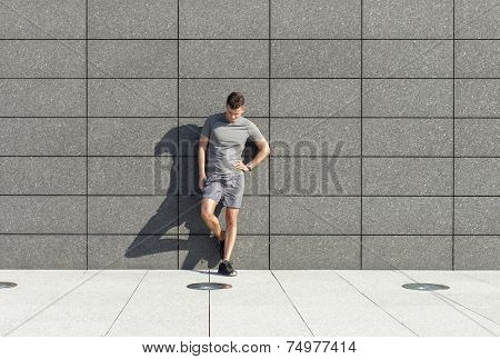Full length of tired sporty man leaning on tiled wall