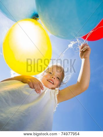 Low angle view of happy young girl holding helium balloons against sky