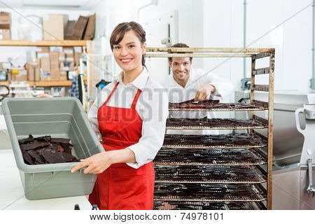 Portrait of beautiful female worker showing beef jerky in basket with colleague standing in background