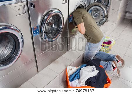 Young man searching clothes inside washing machine drum at laundromat