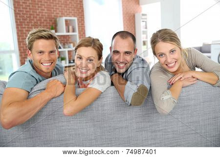 Cheerful roommates sitting in sofa at home
