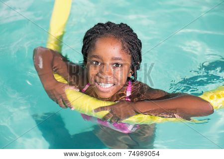 Cute little girl swimming in the pool at the leisure center