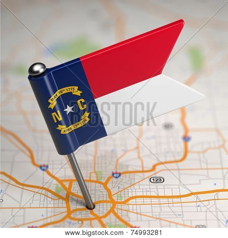 North Carolina Small Flag on a Map Background.