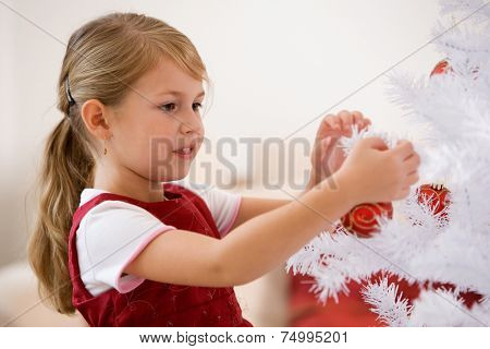 Little girl decorating white christmastree