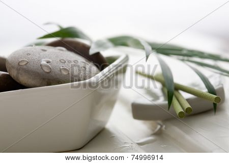 Brown massage stones in white bowl
