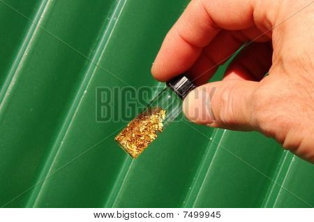 Gold flakes in a vial