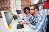 stock photo of side view  - Side view of two photo editors using digitizer in the office - JPG