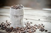 stock photo of sackcloth  - Coffee Beans In The Sackcloth Bag On The Wooden Table - JPG