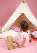 image of teepee tent  - Happy toddler girl engaged in pretend play at home with a teepee tent with a stuffed bear toy - JPG