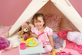 pic of teepee tent  - Happy toddler girl engaged in pretend play tea party indoors at home with a teepee tent - JPG