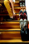 image of ankle shoes  - Photo of a Person sitting and putting on shoes beside Different shoes on a staircase - JPG