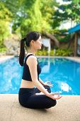picture of padmasana  - Beautiful Asian Girl practicing yoga by the pool lotus pose  - JPG