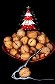 image of walnut-tree  - Wooden bowl full of Walnuts and Hazelnuts with nutcrackers and a pretty tin Christmas tree to the rear England UK Western Europe - JPG