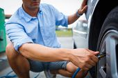 picture of air pressure gauge  - Driver checking air pressure and filling air in the tires of his modern car - JPG