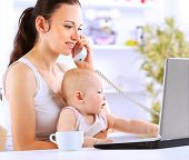 picture of mums  - Mother and baby in home office with laptop and telephone  - JPG