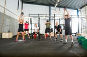 pic of kettlebell  - Group of young male and female athletes lifting kettlebells  - JPG