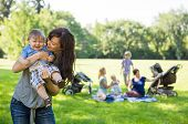 image of mother baby nature  - Mother carrying cheerful baby boy with friends and children in background at park - JPG