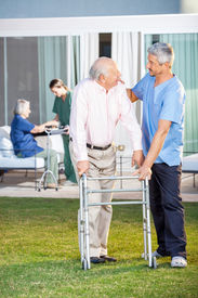 image of zimmer frame  - Male caretaker comforting senior man while assisting him in using Zimmer frame at nursing home lawn - JPG