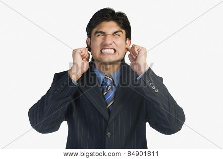 Businessman plugs his ear with finger
