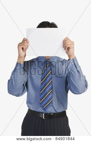 Businessman holding a blank paper in front of his face