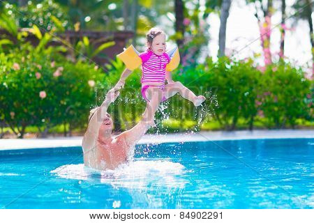 Father And Baby Girl Playing In A Swimming Pool