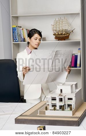 Businesswoman looking at a blueprint in an office