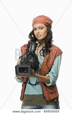 Portrait of a female videographer with video camera
