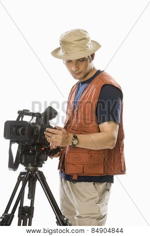 Young male videographer adjusting a videography camera on a tripod
