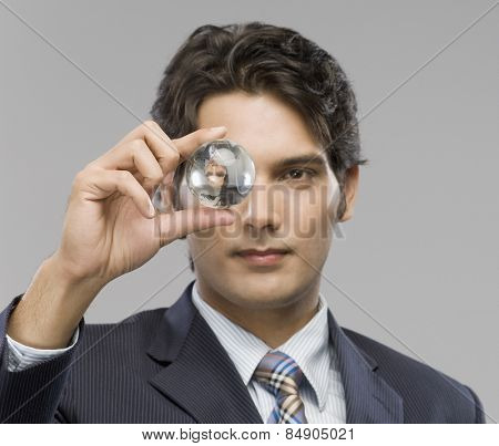 Close-up of a businessman looking at a crystal ball