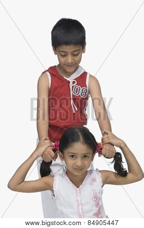Boy pulling hair of his sister