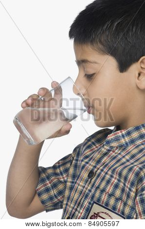 Schoolboy drinking a glass of water