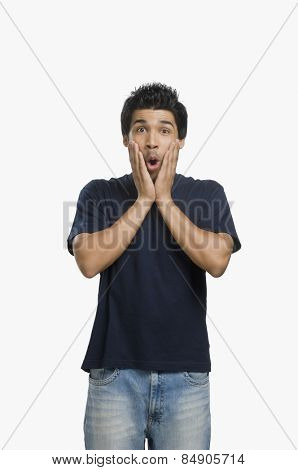 Man looking surprised with his head in his hands