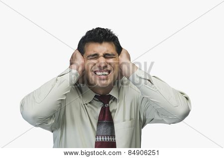 Close-up of a businessman with his hands on his ears