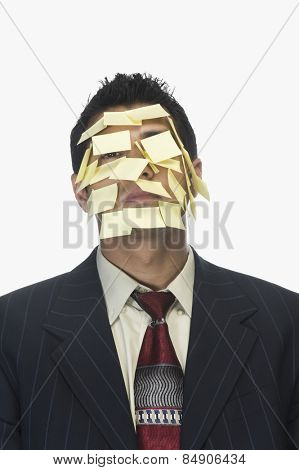 Businessman's face wrapped with adhesive notes