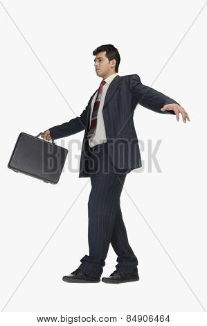Businessman holding a briefcase and walking carefully