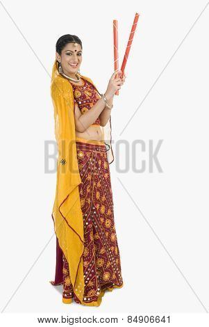 Woman in lehenga choli holding dandiya sticks
