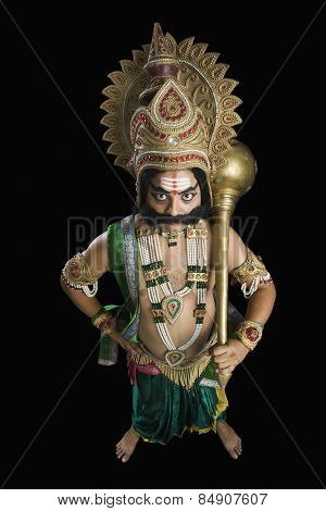 Portrait of a man dressed-up as Ravana and holding a mace