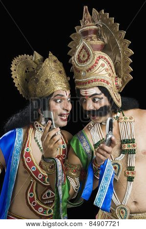 Two stage artists dressed-up as Rama and Ravana and reading text message