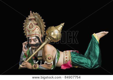 Man dressed-up as Ravana talking on a mobile phone