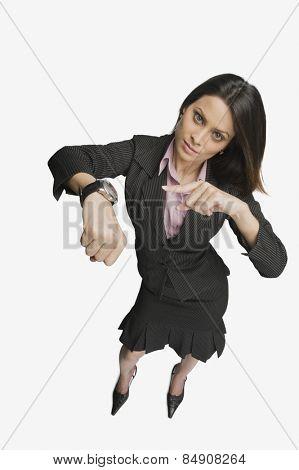 Businesswoman pointing toward a wristwatch