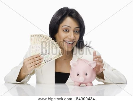 Happy businesswoman holding Indian paper currency and piggy bank