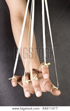 Close-up of a person's hand pulled by threads like a puppet